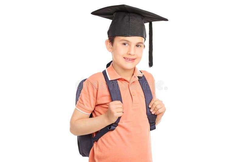 Schooljongen met graduatiehoed die een rugzak dragen royalty-vrije stock foto's