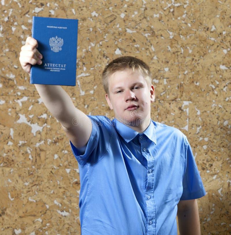 Schooljongen met het certificaat over voltooiing van onderwijs op school royalty-vrije stock afbeeldingen