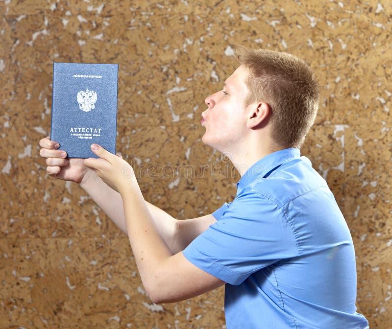 Schooljongen met het certificaat over voltooiing van onderwijs op school royalty-vrije stock fotografie