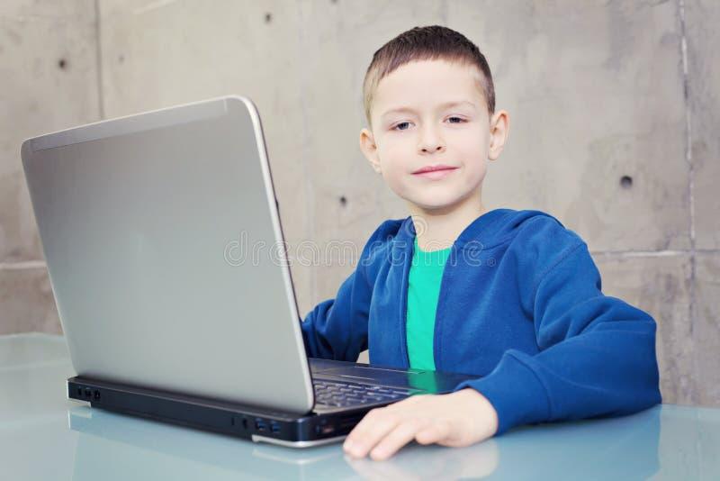 Schooljongen met laptop stock foto