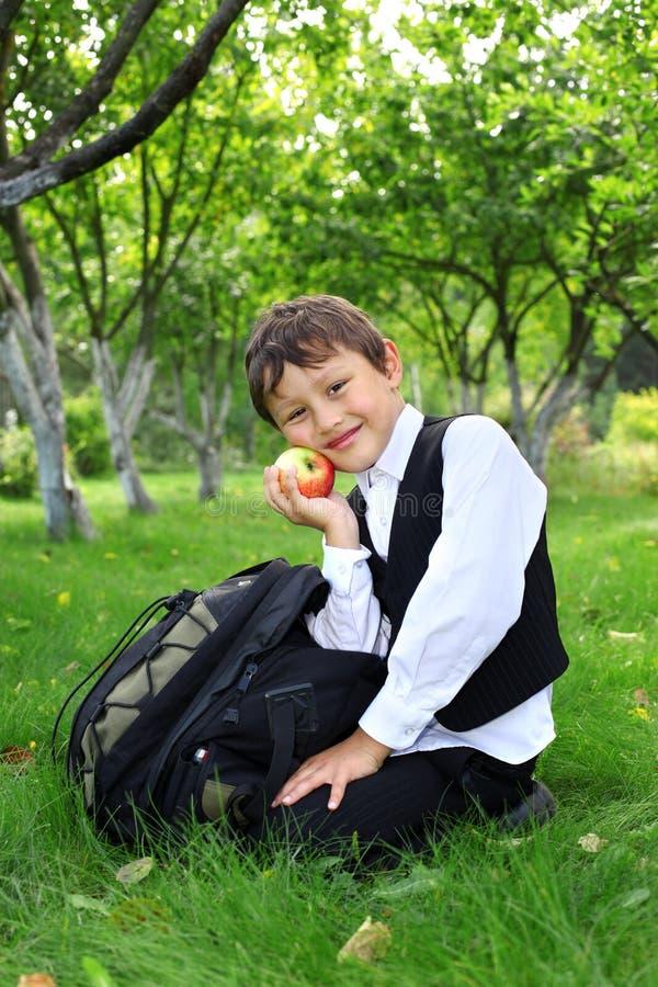 Schooljongen met rugzak en appel royalty-vrije stock afbeeldingen