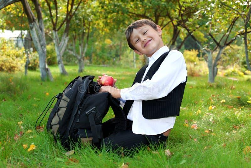 Schooljongen met rugzak en appel royalty-vrije stock afbeelding