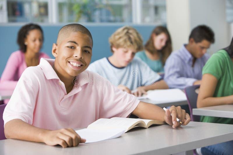 Schooljongen in middelbare schoolklasse stock afbeelding