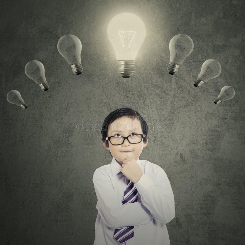 Schooljongen onder heldere lightbulb stock afbeeldingen