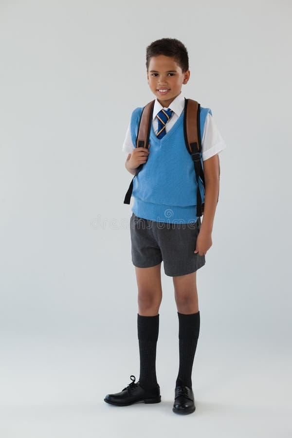 Schooljongen in school eenvormig met schooltas op witte achtergrond stock afbeelding
