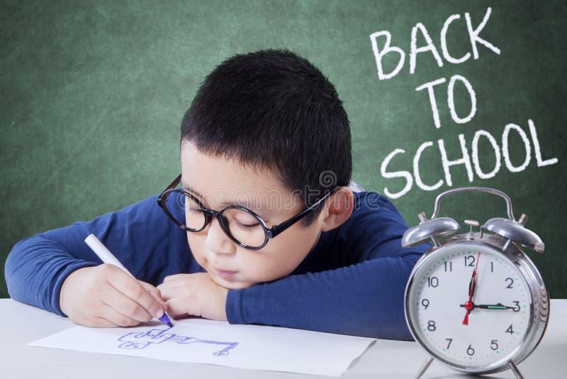 Schooljongen terug naar school en het trekken op bureau royalty-vrije stock afbeelding