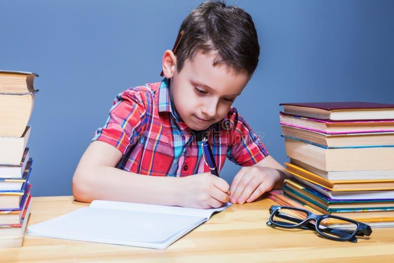 Schooljongenstudie op school, thuiswerk het leren stock foto