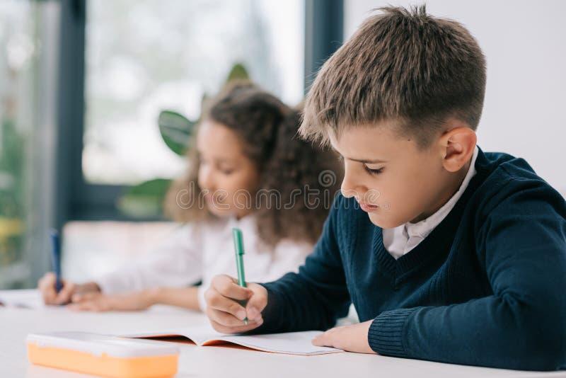Schooljongenzitting bij bureau en het schrijven in oefenboek met klasgenoot erachter zitting stock afbeeldingen