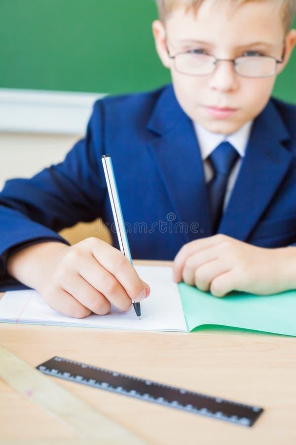 Schooljongenzitting bij bureau op school en het schrijven aan notitieboekje stock foto