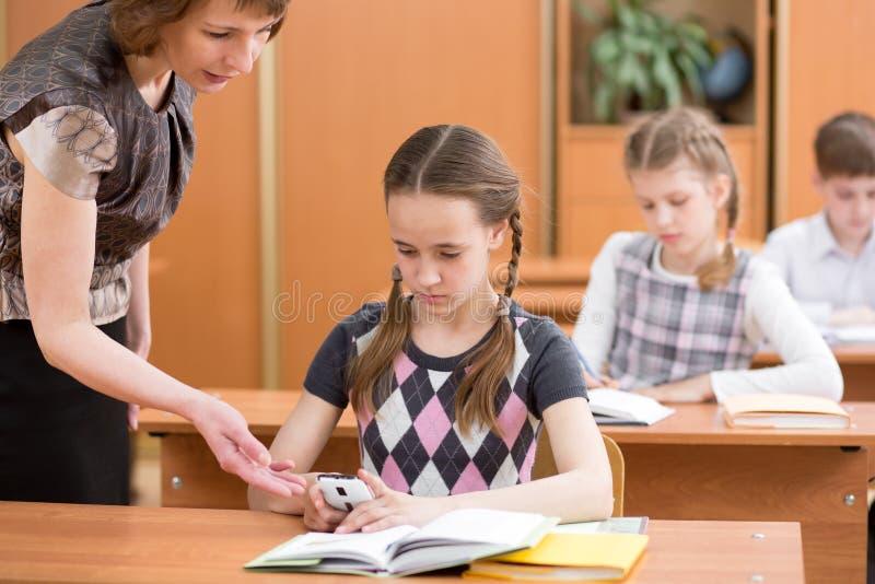 Schoolkid& de confiscação x27 do professor; telefone celular de s na lição imagens de stock royalty free