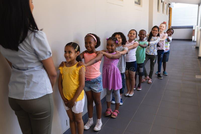 schoolkids正面图有站立在行的老师的用他们的在肩膀的手在走廊 免版税库存图片