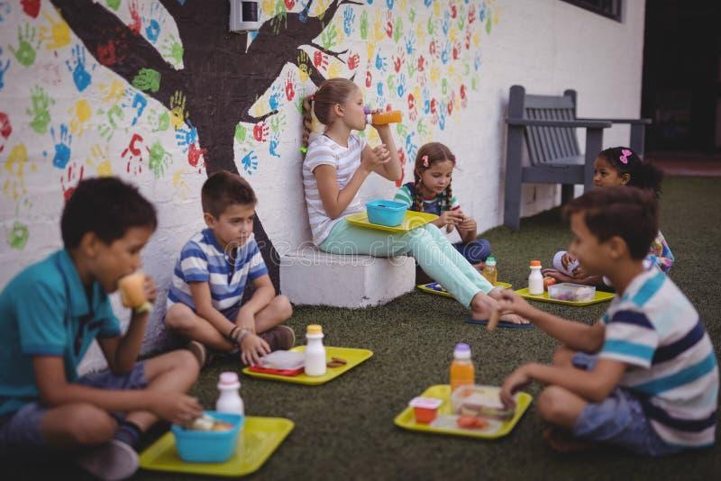 Schoolkids имея еду стоковая фотография rf