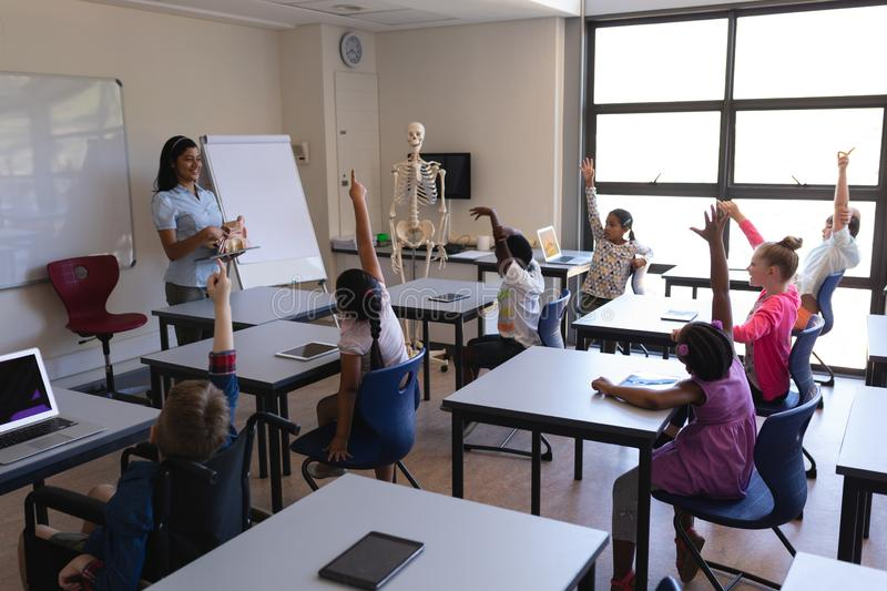 Schoolkids raising hands while sitting at desk in classroom royalty free stock image