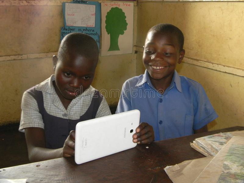 Schoolkids using Samsung tablet. Norton,Zimbabwe,27September 2017. Two primary school chilsdren in school uniforms using a Samsung tablet during study time royalty free stock photo