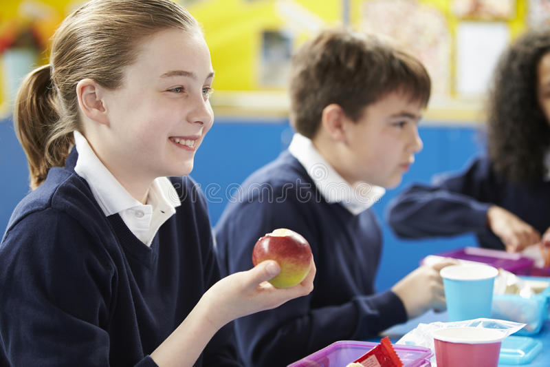 Schoolkinderen die bij Lijst zitten die Ingepakte Lunch eten stock afbeelding