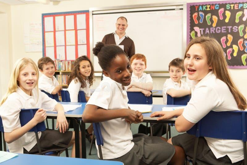Schoolkinderen die in Klaslokaal bestuderen stock foto's