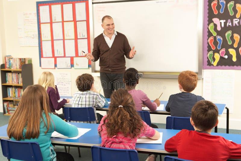 Schoolkinderen die in Klaslokaal met Leraar bestuderen royalty-vrije stock foto