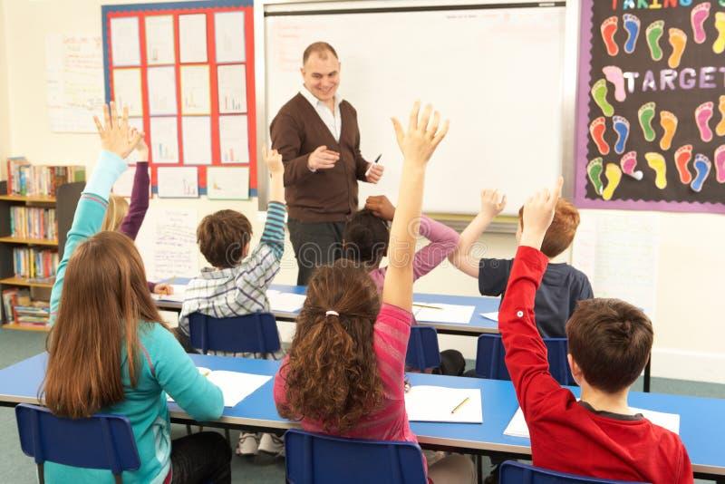 Schoolkinderen die in Klaslokaal met Leraar bestuderen royalty-vrije stock foto's