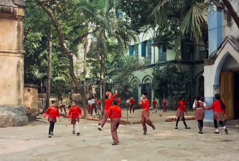 Schoolkinderen die met frisbee in groene binnenplaats van school springen stock afbeelding