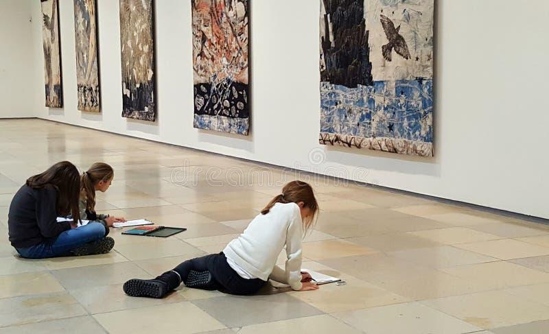 Schoolkinderen die op de vloer van kunsttentoonstelling schetsen in Haus der Kunst, München Duitsland Onderwijskunstenproject royalty-vrije stock afbeeldingen