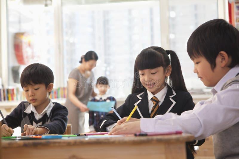 Schoolkinderen die tijdens kunstklasse trekken, Peking stock afbeelding