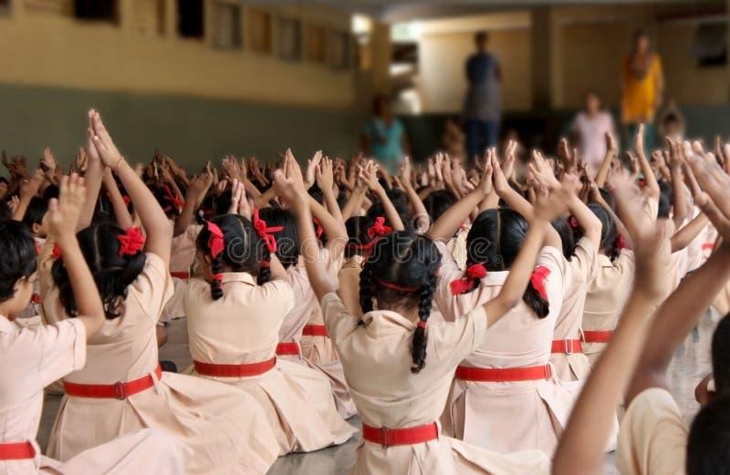 Schoolkinderen die yoga met de leraren doen stock afbeeldingen