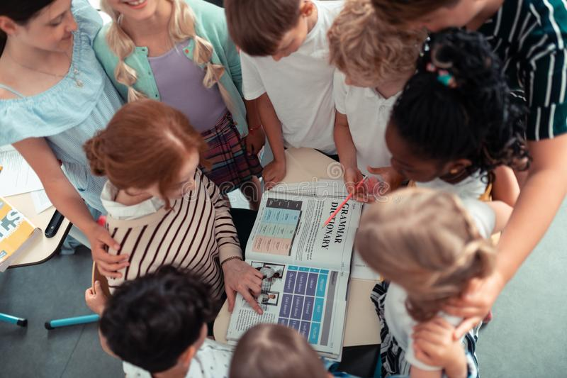 Schoolkinderen die zich rond hun regels van de leraarslezing bevinden stock afbeeldingen