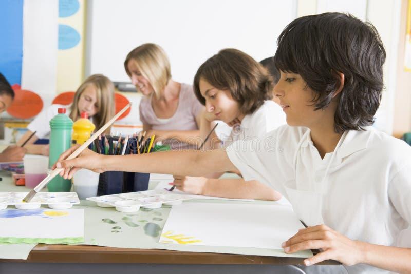 Schoolkinderen en hun leraar in een kunstklasse stock afbeeldingen