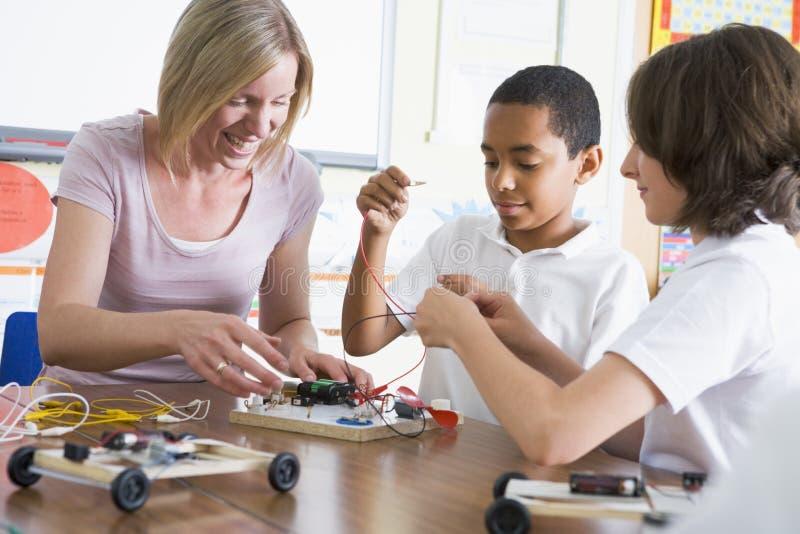 Schoolkinderen en hun leraar het leren wetenschap stock afbeelding