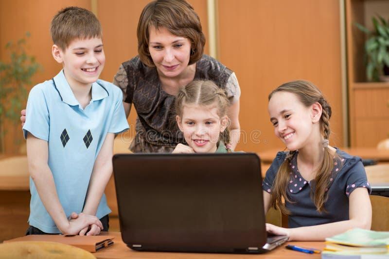 Schoolkinderen en leraar die notitieboekje gebruiken bij les royalty-vrije stock foto
