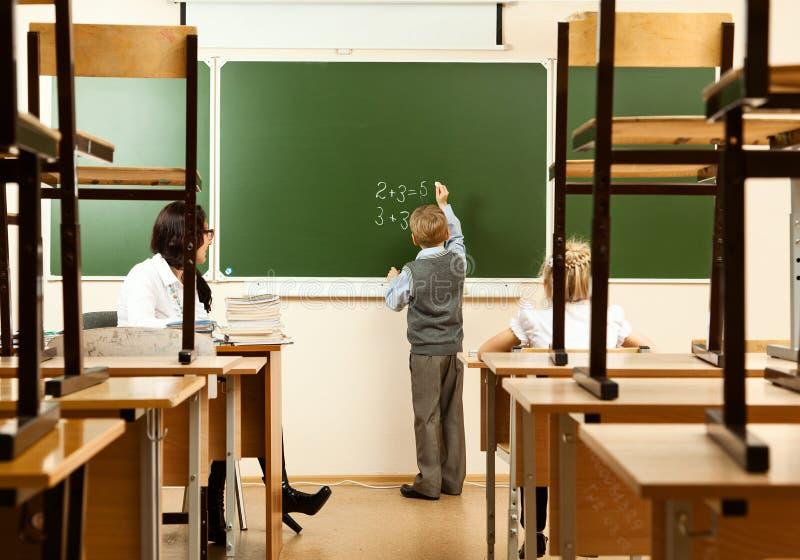 Schoolkinderen in het halve lege klaslokaal stock afbeeldingen