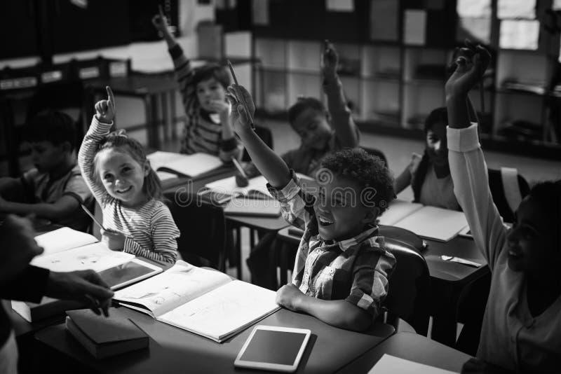 Schoolkinderen hun opheffen dient klaslokaal in stock fotografie