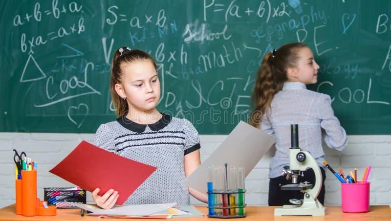 Schoolklassen De meisjes bestuderen chemie in school De chemische reacties van microscoopreageerbuizen Leerlingen bij bord royalty-vrije stock afbeeldingen