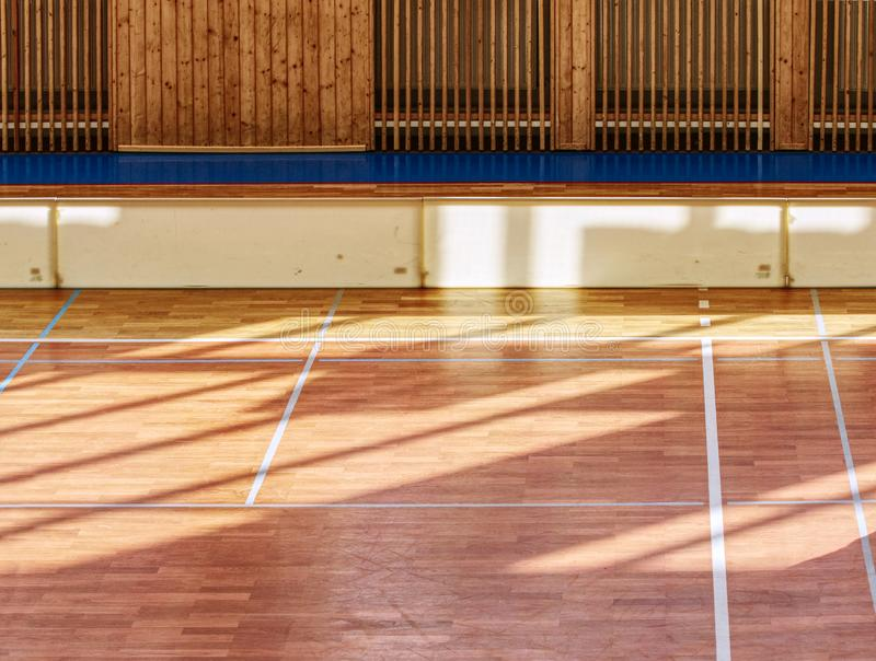 Schooll gym hall with heating system over wooden bars cover. Schooll gym hall with water heating system hidden over wooden bars cover.  Basketball court. Lines royalty free stock photos