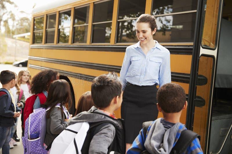 Schoolleraar die jonge geitjes op de schoolbus te krijgen voorbereiden stock afbeeldingen