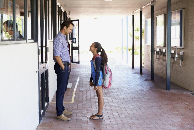 Schoolleraar die met schoolmeisje buiten klaslokaal spreken stock foto