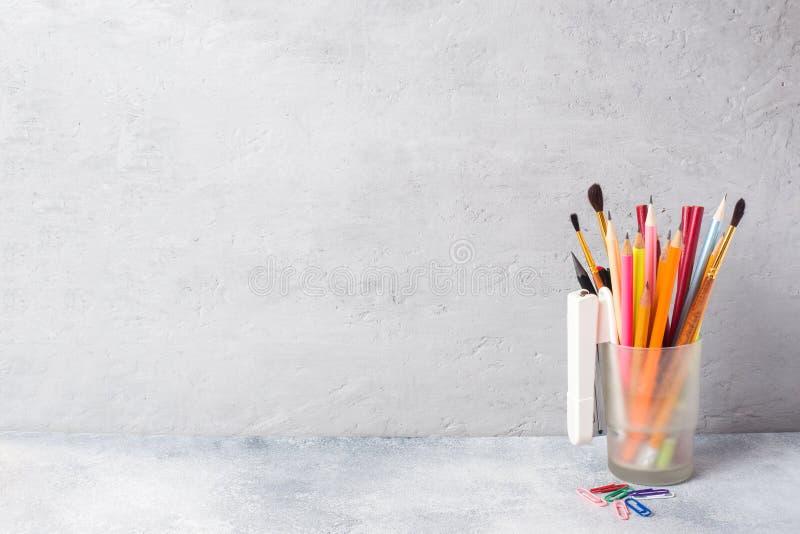 Schoollevering, een reeks potloodtellers in een glas op een grijze lijst met een exemplaar van ruimte Conceptenschool stock foto