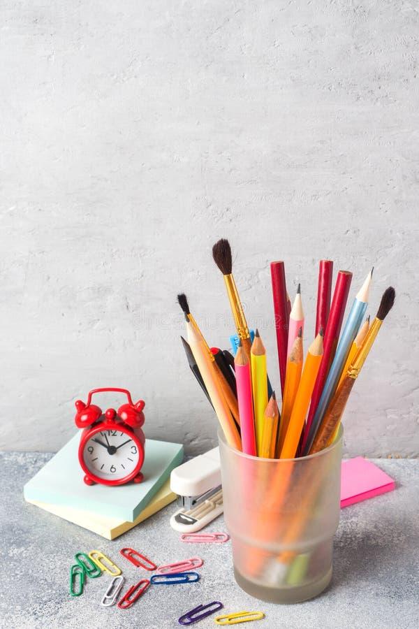 Schoollevering, een reeks potloodtellers in een glas op een grijze lijst met een exemplaar van ruimte Conceptenschool stock afbeelding