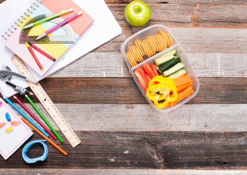 Schoollevering en lunch op houten achtergrond stock afbeelding