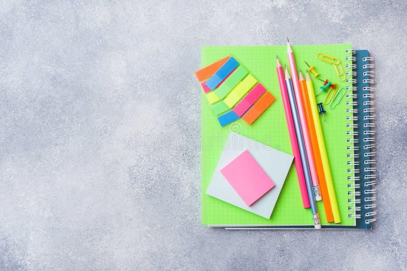 Schoollevering, notitieboekjespotloden op grijze achtergrond met exemplaarruimte stock fotografie