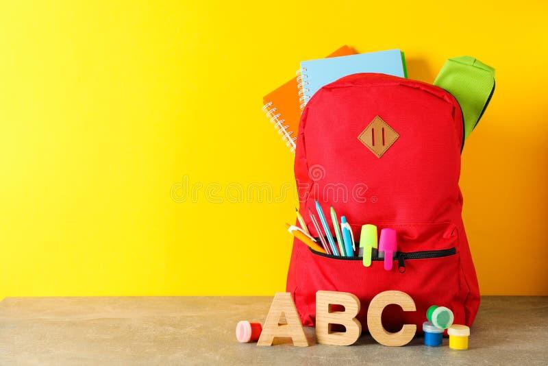 Schoollevering op grijze lijst tegen kleurenachtergrond stock afbeelding