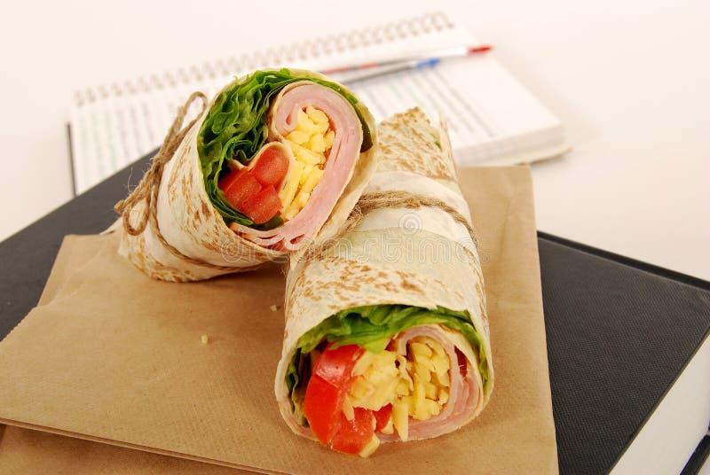 Schoolmaaltijd: ham en kaasomslagsandwich met lunchzak op het boek stock foto