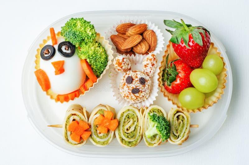 Schoolmaaltijddoos voor jonge geitjes met voedsel in de vorm van grappige gezichten stock foto's