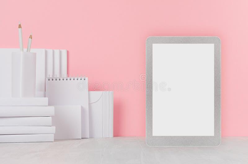 Schoolmalplaatje - witte boeken, kantoorbehoeften, lege stickers en tabletcomputer op wit bureau en zachte roze achtergrond stock afbeelding