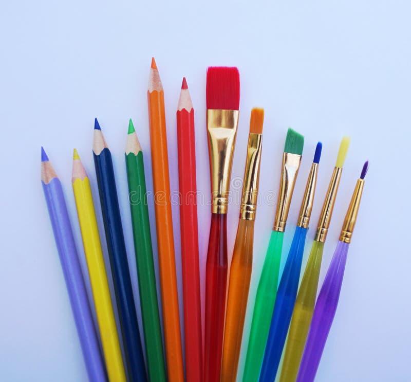 Schoolmateriaal voor kunstonderwijs, houten kleurenpotlood en verfborstels in verscheidene kleuren royalty-vrije stock afbeeldingen