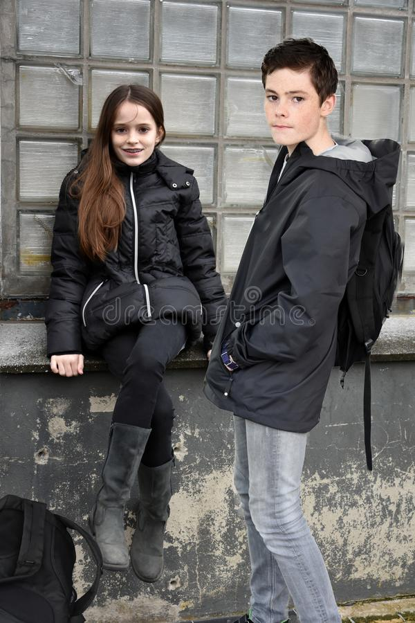 Schoolmates in a corner of the schoolyard. School friends in a corner of the schoolyard before the lesson begins . Both dressed in black royalty free stock photography