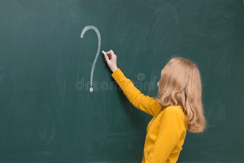 Schoolmeisje bij bord met vraagteken stock fotografie