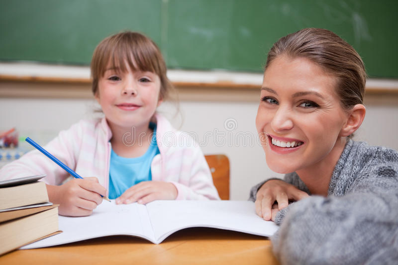 Schoolmeisje dat met haar leraar schrijft stock foto's
