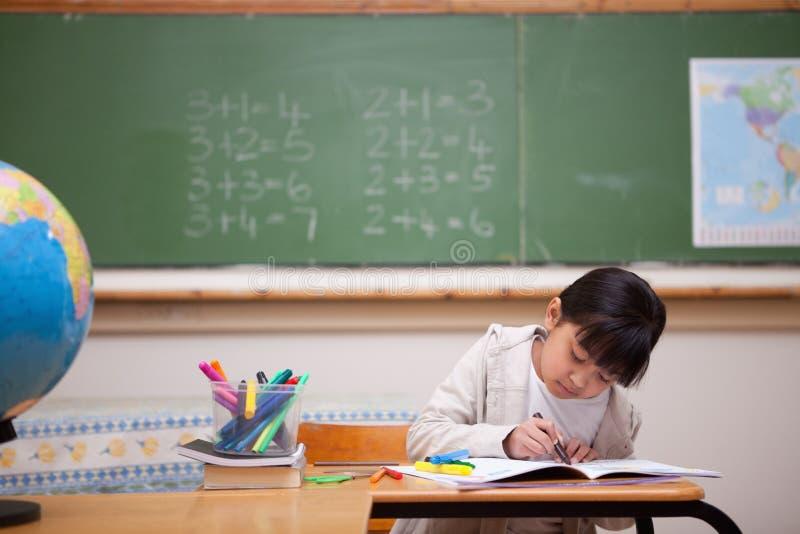 Schoolmeisje dat op een kleurend boek trekt stock afbeeldingen