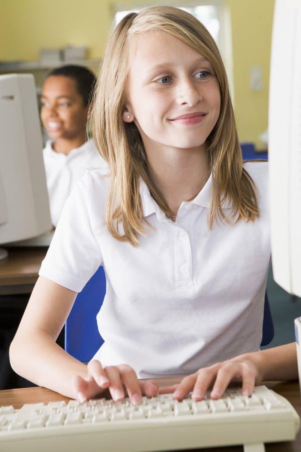Schoolmeisje dat voor een schoolcomputer bestudeert royalty-vrije stock fotografie